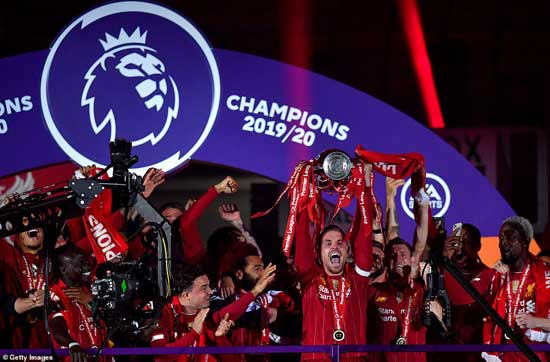 Liverpool captain Jordan Henderson and his team-mates lifted the trophy on a custom-built stage on the Kop but with no fans in attendance.