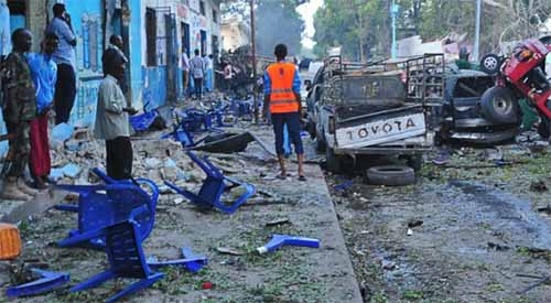 People stand among damages at the scene of a blast after two car bombs exploded in Mogadishu on October 28, 2017. © MOHAMED ABDIWAHAB/AFP