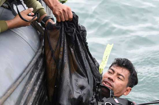 Indonesia Navy diver recovers what are believed to be remains from Sriwijaya Air flight SJ 182 which crashed into the sea, at Jarkarta International Container Terminal port in Jarkarta, Indonesia, January 10, 2021. Reuters photo
