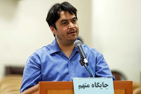 "In this June 2, 2020 photo, journalist Ruhollah Zam speaks during his trial at the Revolutionary Court, in Tehran, Iran. Iran. The judiciary spokesman, Gholamhossein Esmaili, announced Tuesday, June 30, 2020 that Zam, a journalist whose online work helped inspire the 2017 economic protests and who returned from exile to Tehran was sentenced to death. The Persian writing on the podium reads, ""defendant's place."" (Ali Shirband/Mizan News Agency via AP)"