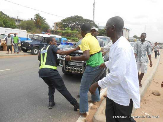 A Ghana Police officer (L) fights with a taxicab driver following a dispute between the two. Photo credit – Empress on the road